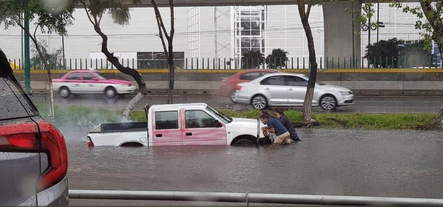 Una camioneta Nissan se quedó varada en la inundación en Viveros de la Loma, Tlalnepantla