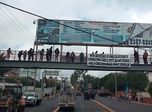 En un puente, presuntos golpeadores y la lona en que supuestamente vecinos apoyan la obra, pero fue colocada por trabajadores del Ayuntamiento de Atizapán