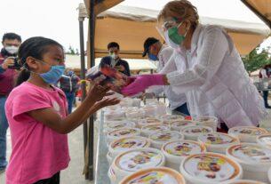 Ruth Olvera Nieto entrega comida caliente a una niña para que mejoren la dieta